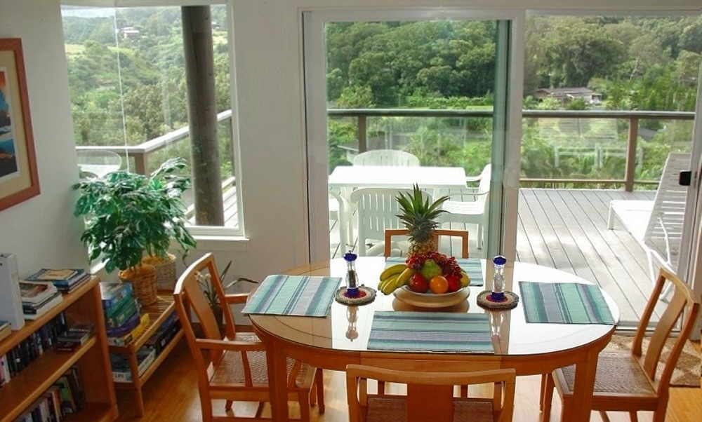 Dining table overlooking rainforest in a Maui cottage rental